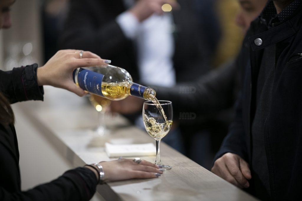 Un serveur sert un verre de Jurançon