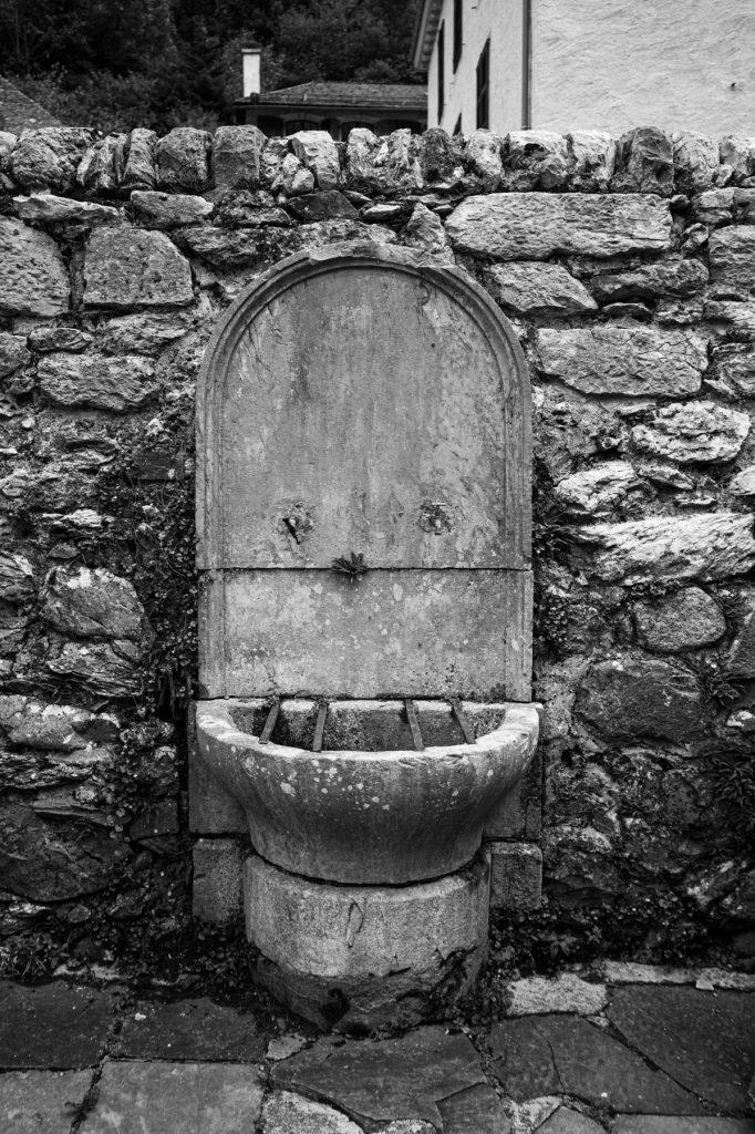 Fontaine municipale abandonnée. Une goute tombe d'un robinet vissé à l'envers. Cette fontaine ressemble étrangement à un visage