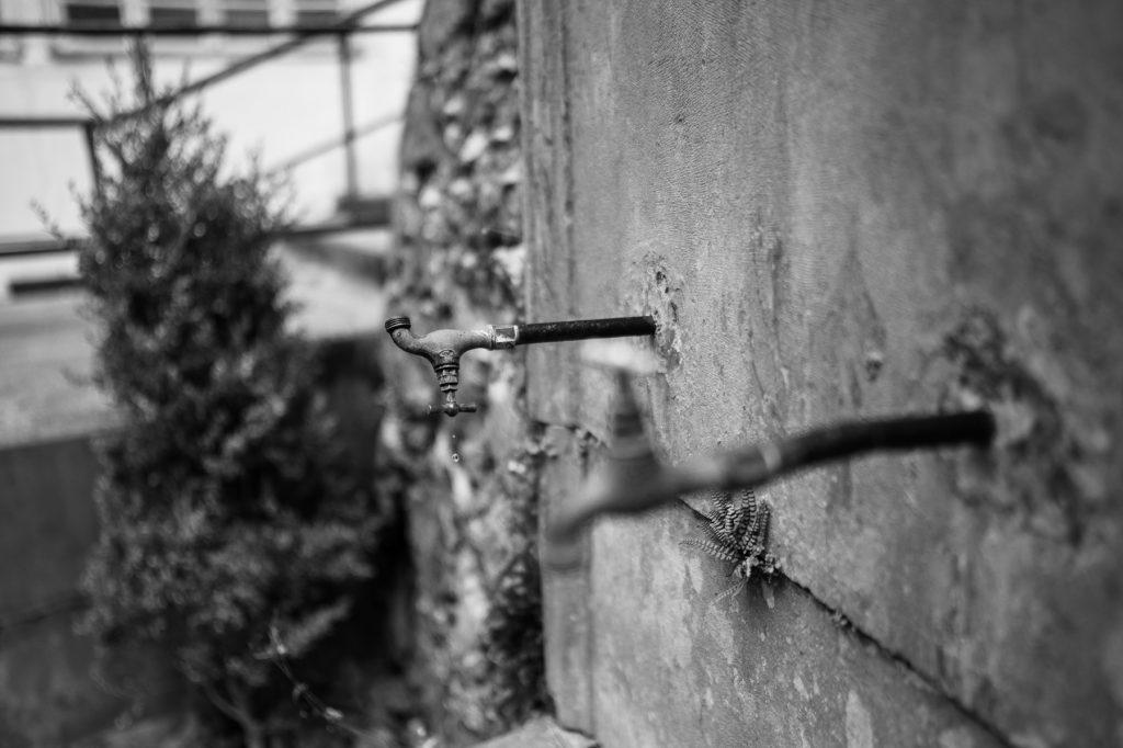 Robinets d'une fontaine municipale abandonnée. Une goute tombe d'un robinet vissé à l'envers
