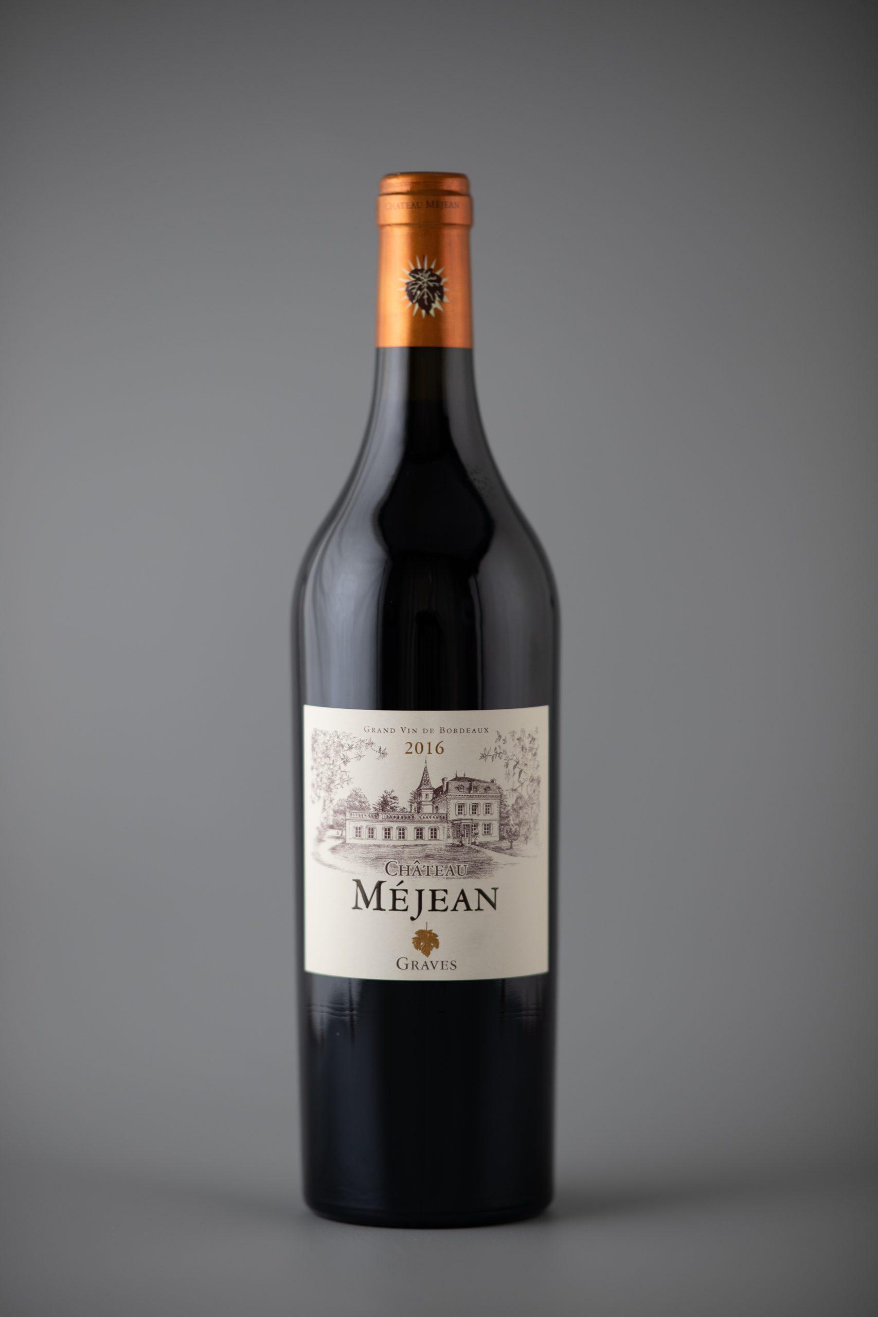 Photographie d'une bouteille de vin rouge sur un fond gris mat