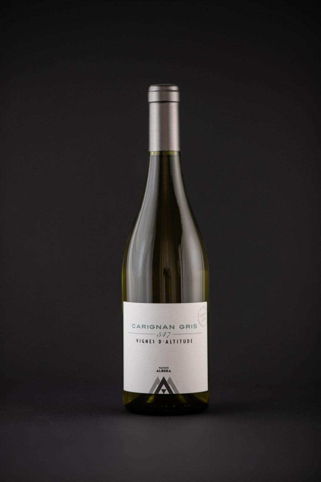 Photographie d'une bouteille de vin blanc sur un fond noir mat