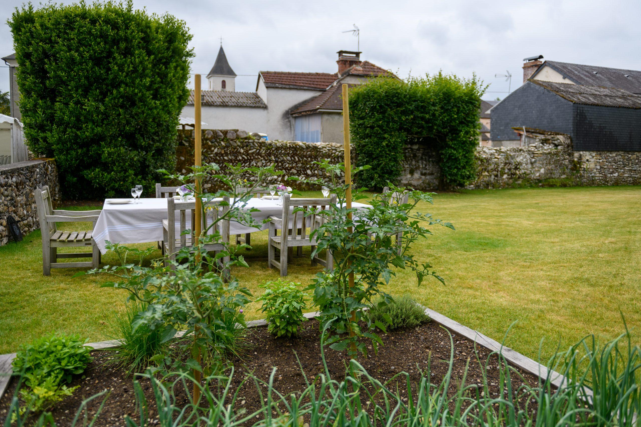 Table dans un cadre champêtre à c^ôté d'un superbe potager pour les convives invités à déguster des produits frais cuisinés sur le brasero Lierre Edition