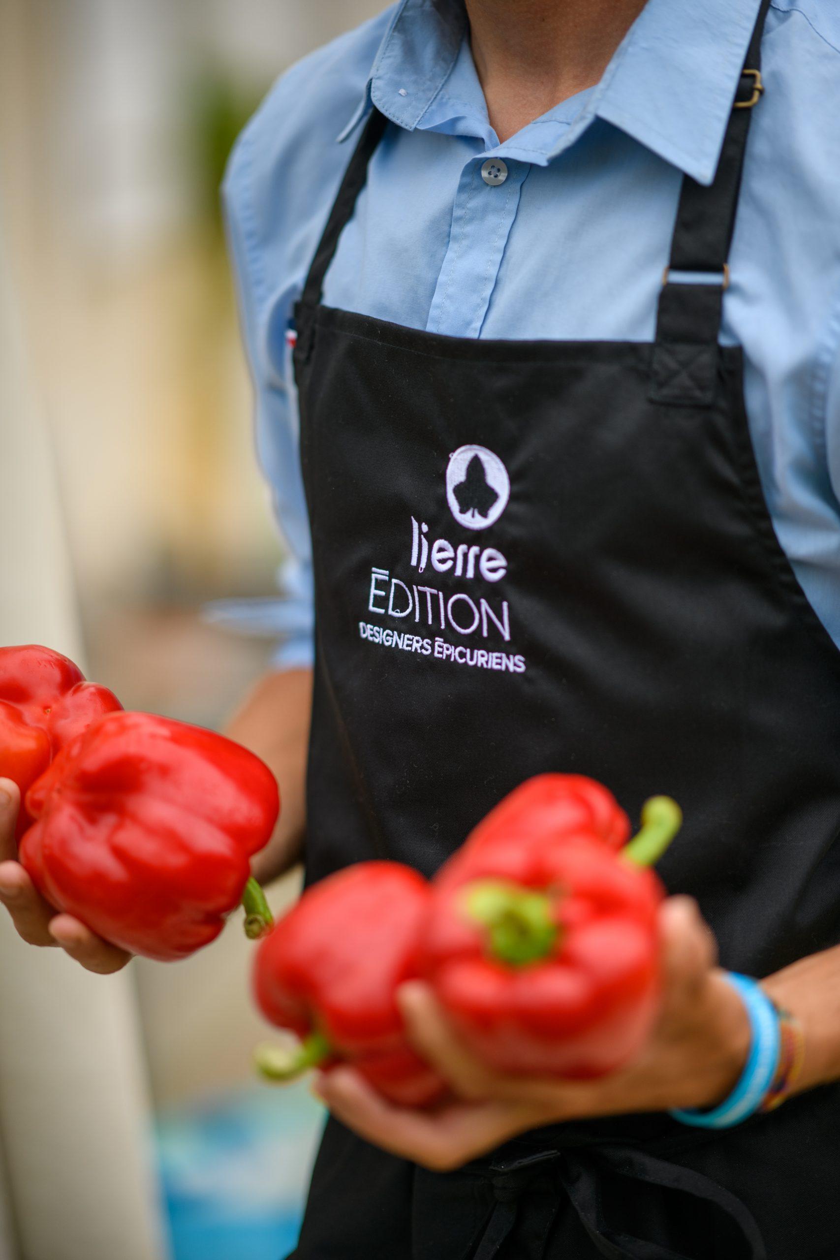 Un cuisinier apporte des poivrons rouges qui seront cuisinés sur le braséro Lierre Edition