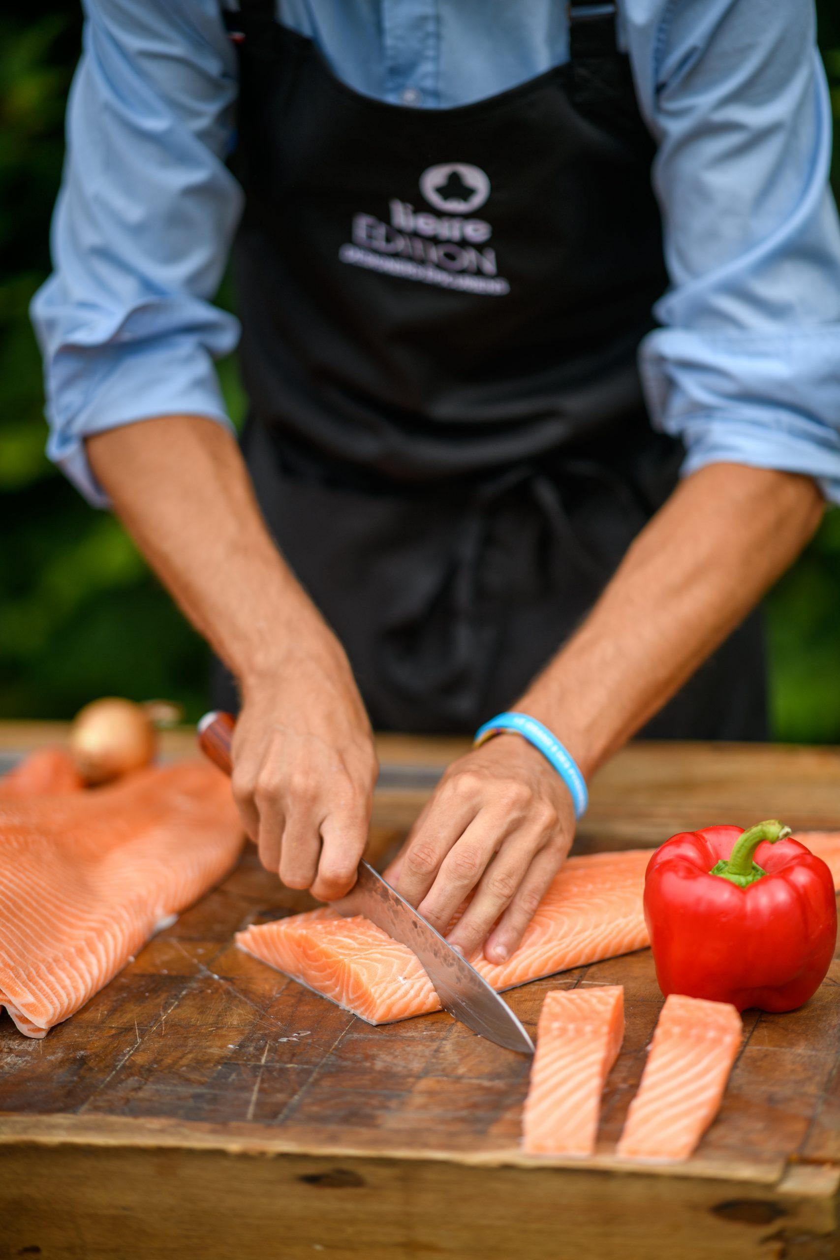 Un cuisinier coupe des tranches de saumon sur un plan de travail en bois qui seront cuisinés sur le braséro Lierre Edition