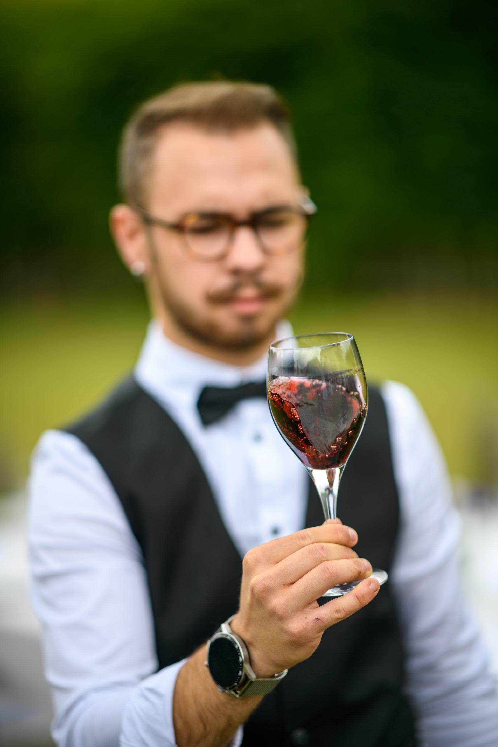 Un sommelier fait tourner un vin rouge dans son verre