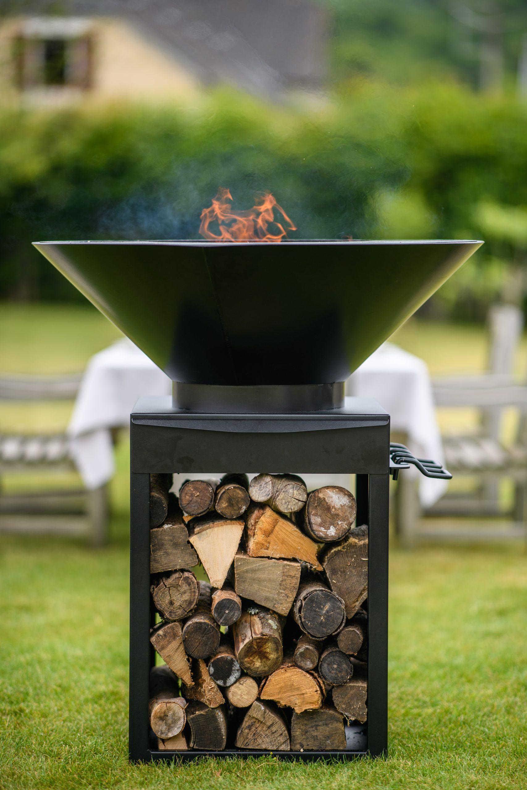 Le brasero Lierre Edition vu de côté. Le feu est allumé et nous apercevons le système de stockage de bois